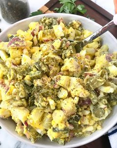 Potato salad with eggs, pickles, red onion and creamy dressing in a white bowl with a silver spoon ready to be served