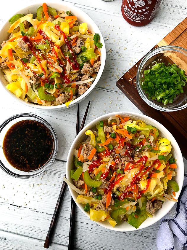 2 white bowls filled with sauteed cabbage, ground turkey, celery, carrots, white onion and bean sprouts sitting next to a sweet Asian sauce