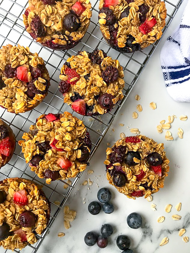 Baked mixed berry oatmeal cups sitting on a silver metal cooling rack with blueberries and dry oats scattered around