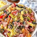 Angle view of Italian pasta salad in a large bowl sitting next to a blue checkered cloth
