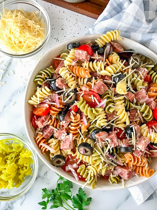 Pasta salad in a white bowl sitting next to a small bowl of pepperoncinis and a small bowl of parmesan cheese