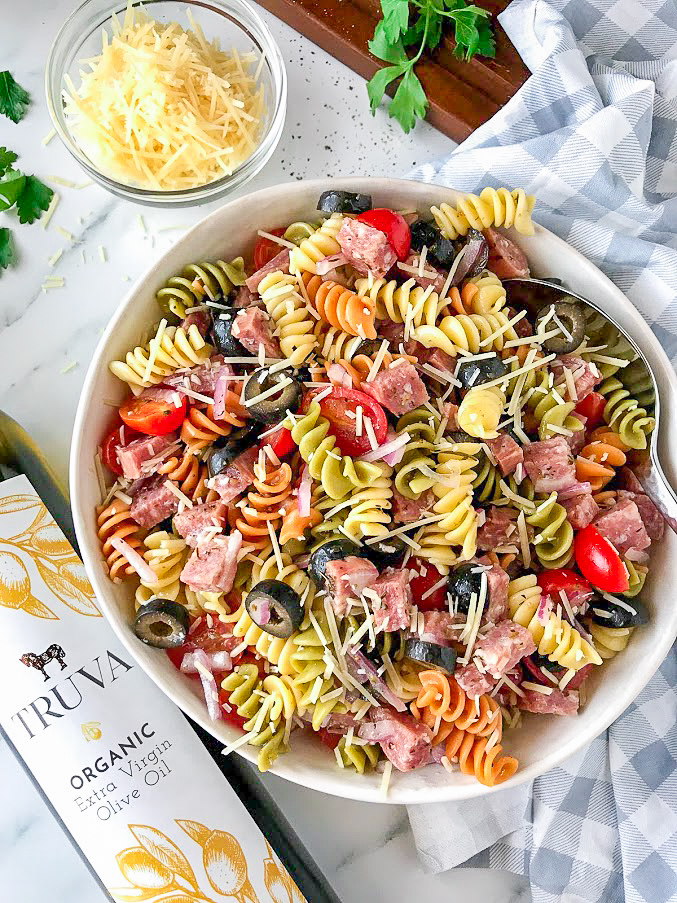 Pasta salad with salami, tomatoes, black olives, onion and parmesan cheesse tossed in a red wine vinegar vinaigrette in a white bowl next to a bottle of extra virgin olive oil