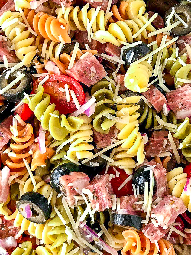 Close up of noodles, salalmi, grape tomatoes, olives, onion and parmesan cheese