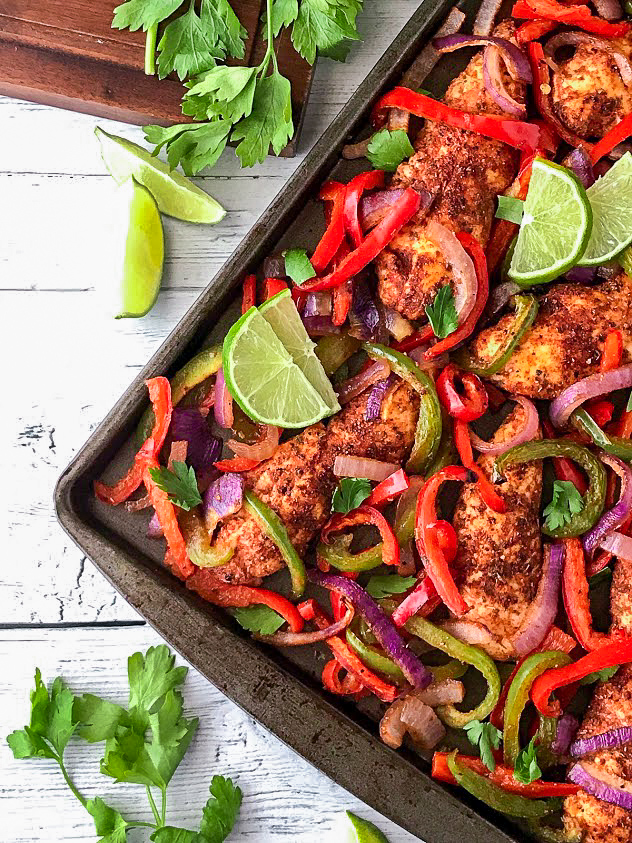Chicken tenders, peppers and onions seasoned with fajita spices on a dark baking sheet with limes and cilantro scattered around