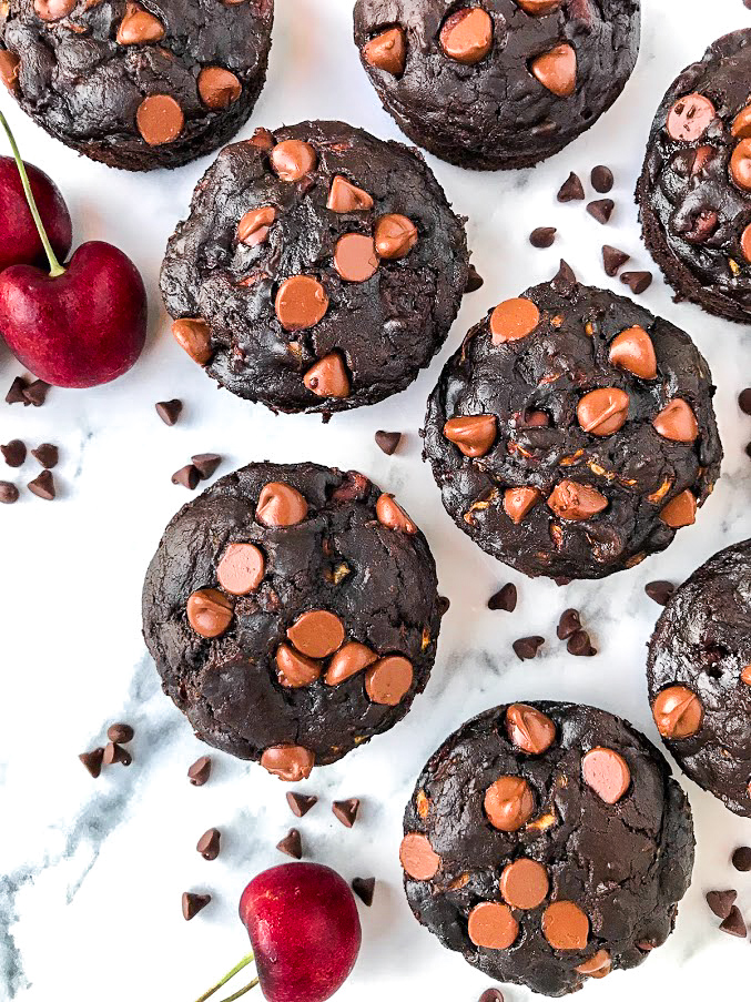 Close up picture of 8 double chocolate chip muffins sitting on a marble board next to mini chocolate chips and three red cherries with green stems