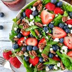 Side picture of a fresh summer salad with homemade strawberry balsamic vinaigrette sitting next to a silver fork and 2 strawberries