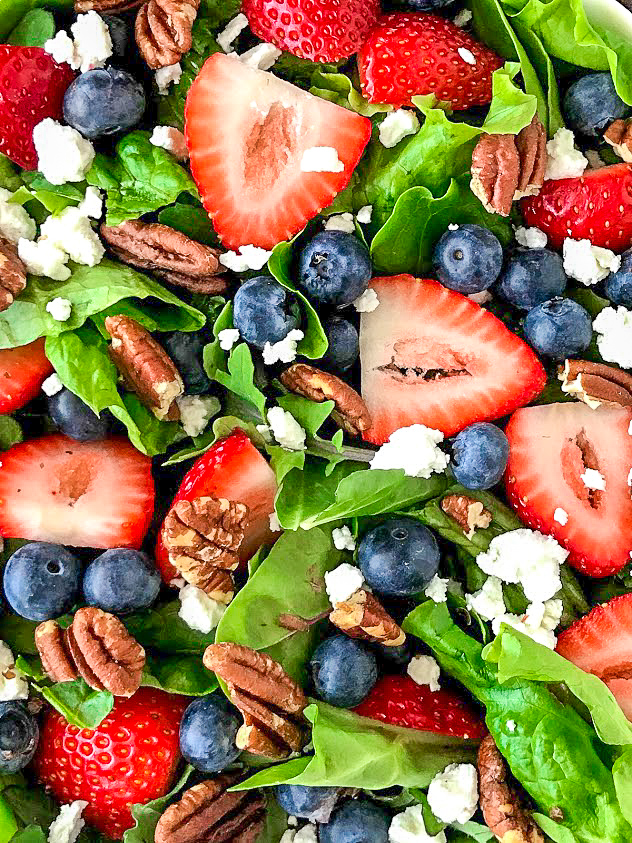 Close up picture of a strawberry, blueberries, goat cheese and toasted pecan salad