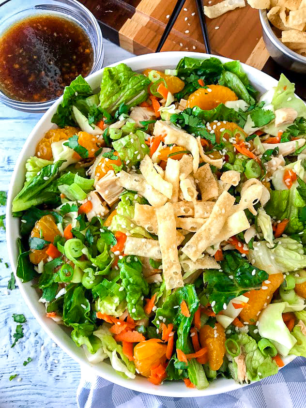Side view of a white bowl filled with lettuce , cabbage, shredded carrots, mandarin oranges, chicken, cilantro and wonton strips sitting next to a soy vinaigrette dressing