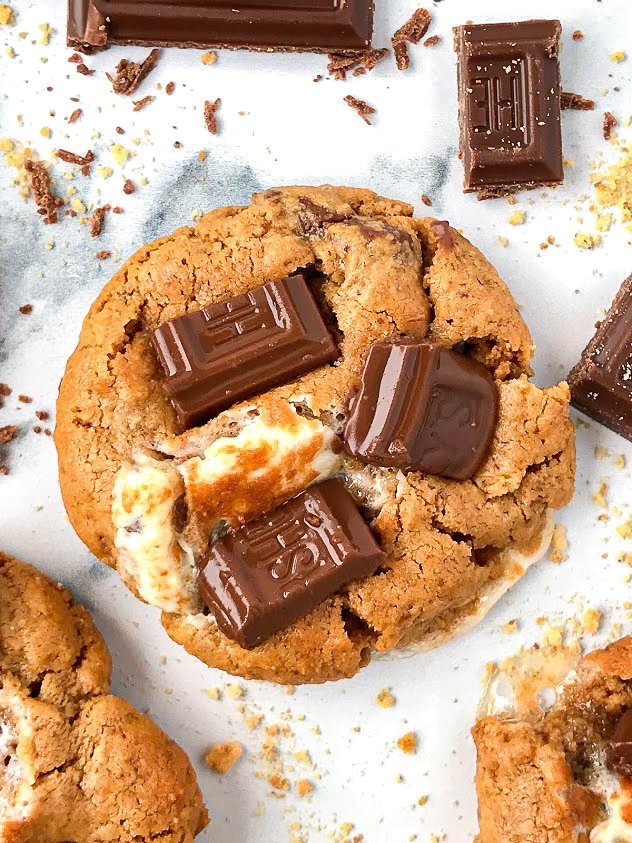 Close up picture of a s'mores cookies with chocolate pieces and cookie crumbles scattered around