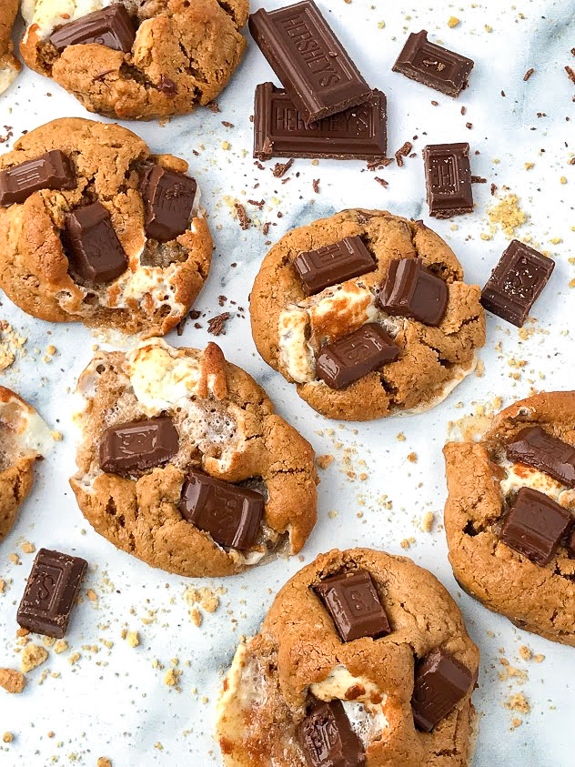 6 cookies made with graham crackers, chocolate and marshmallows sitting on a marble counter top