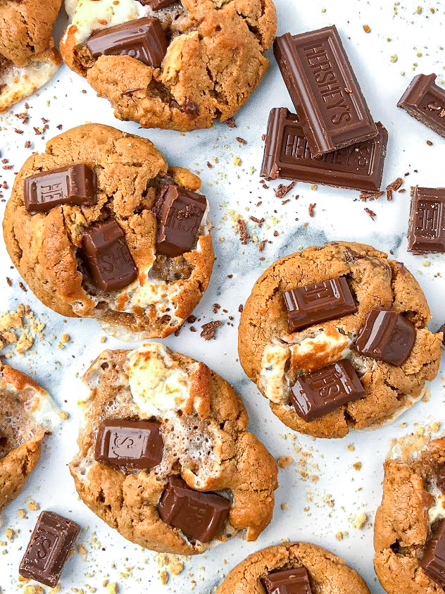 Close up of 3 s'mores cookies on a white marble background with crushed graham crackers and crumbled chocolate pieces scattered around