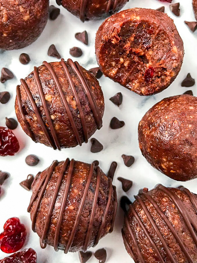 2 chocolate cherry protein balls drizzled with melted dark chocolate sitting next to 1 ball with a bite taken out of it