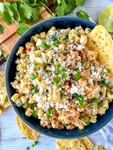 Easy Mexican corn dip made with sweet corn, green chiles, cotija cheese, light sour cream, lime juice, cilantro and chili powder in a blue bowl.