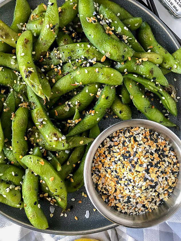 Close up picture of edamame covered in everything seasoning sitting next to a small bowl of everything seasoning