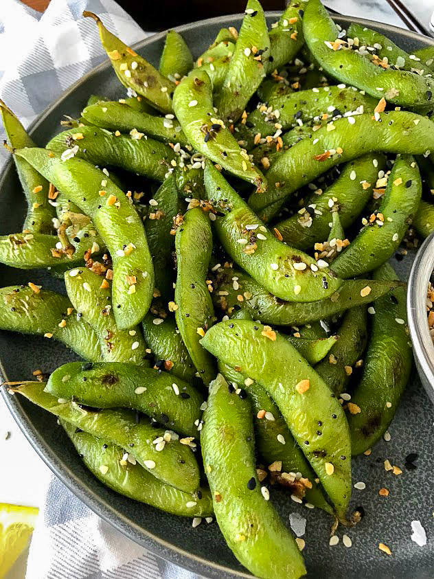 Homemade edamame made with lemon and garlic sitting on a gray plate