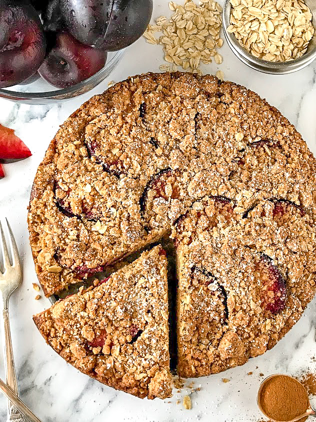 A full picture of plum coffee cake with a crumble topping and small dusting of powdered sugar. It's sitting next to a bowl of plums and a spoonful of cinnamon.