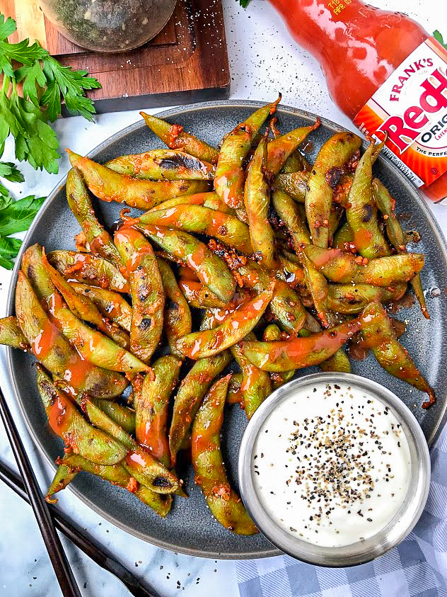 A picture of easy buffalo edamame sitting on a gray plate next to a small bowl of ranch. It's perfect for a healthy game day snack or appetizer!