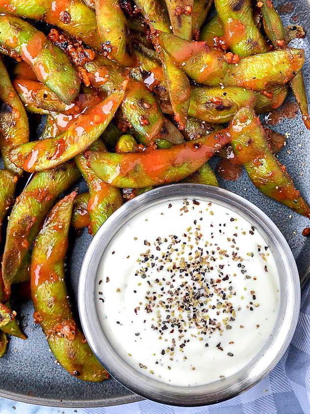 Sauteed soybeans drizzled in a homemade spicy sauce sitting next to a small silver bowl that's filled with ranch dressing and topped with black pepper flakes.