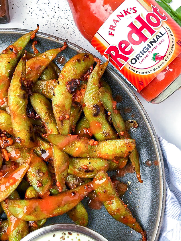 Easy buffalo edamame that's been sauteed with garlic, Frank's red hot sauce and butter. The edamame is laid out on a plate next to a bottle of hot sauce.