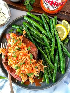 A delicious and healthy meal featuring shredded buffalo chicken stuffed into a baked sweet potato and served with sauteed green beans