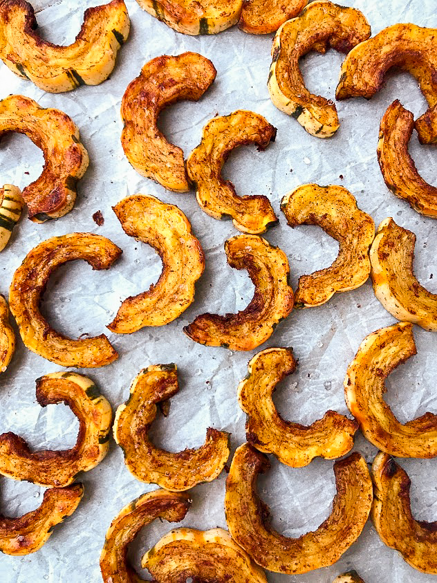 A tray of delicata squash that's been cut into slices and roasted with cinnamon and salt. Roasted delicata squash is a great healthy snack option.