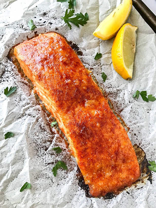Cooked salmon with a sweet maple glaze sitting on a baking sheet lined with parchment paper with lemons and parsley
