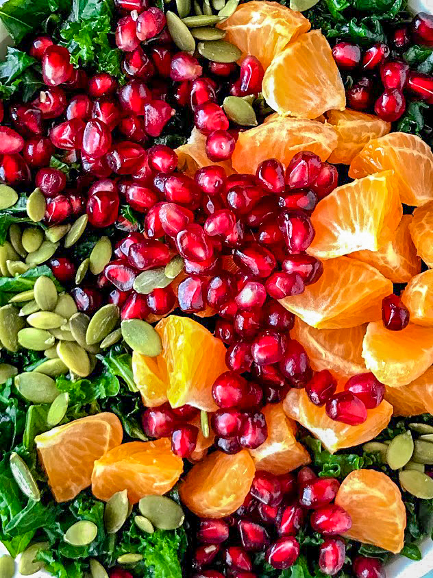 A close up photo of pomegranate seeds, clementine oranges, chopped kale that's been massaged in lemon juice and toasted pepitas.