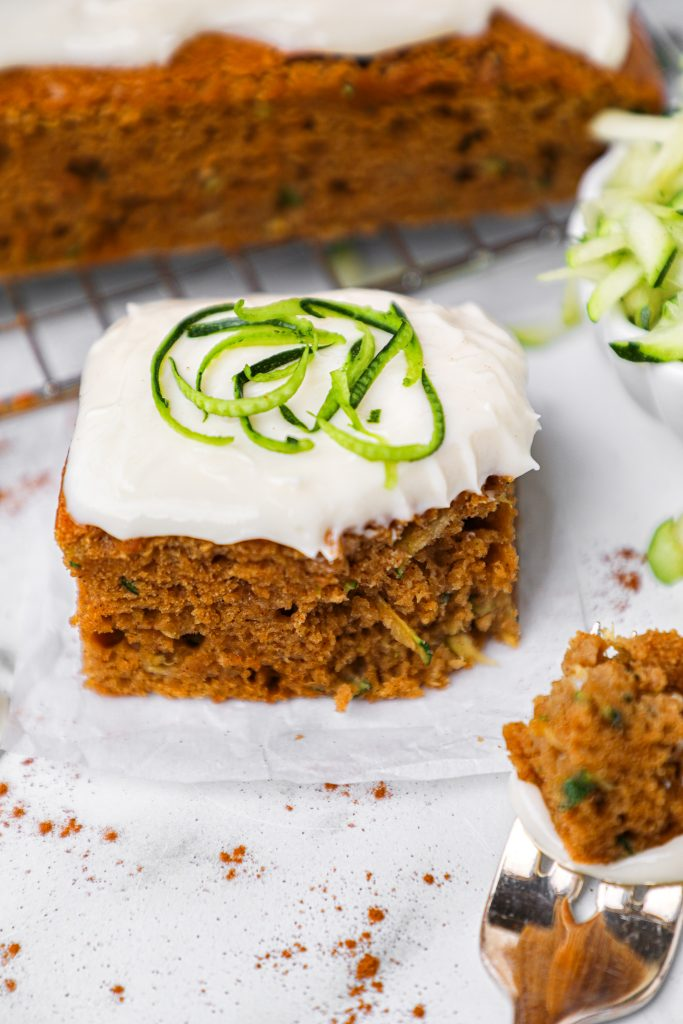 An angle view of a piece of healthier spiced zucchini cake with cream cheese frosting and a bite taken out of one side. It's the perfect healthy treat!