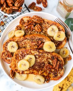 Sourdough french toast made by dipping bread in a mixture of mashed bananas, almond milk, an egg and cinnamon. It's also served with sauteed bananas and candied pecans.