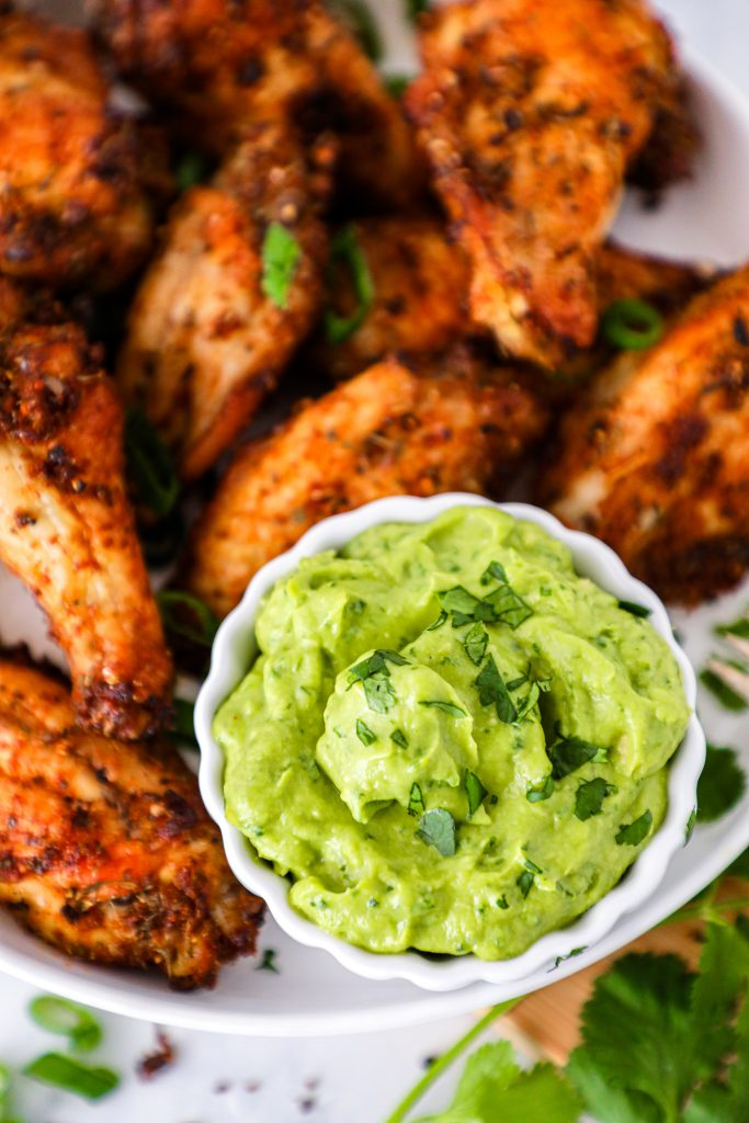 Easy spicy chicken wings served with a tangy avocado cilantro lime sauce! This sauce is a great option for anyone that's dairy free and it pairs perfectly with Cajun seasoning!