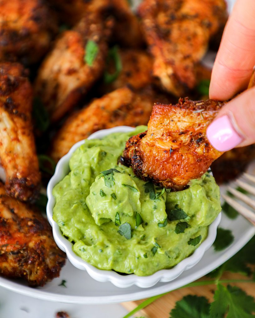 Easy instructions for how to make baked and air fried chicken wings. These are seasoned with a homemade spice mix and served with a creamy avocado sauce! There's no need for ranch with these wings and they'd be perfect for the Super Bowl!
