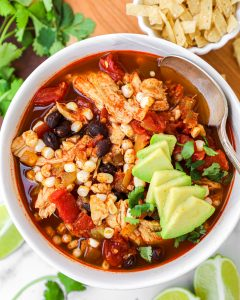 Healthy chicken enchilada soup made in the crock pot. This slow cooker recipe is easy, delicious and perfect for a lazy night in!