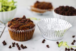 A picture of a double muffin liner with an outer aluminum liner sitting next to a chocolate chip muffin.
