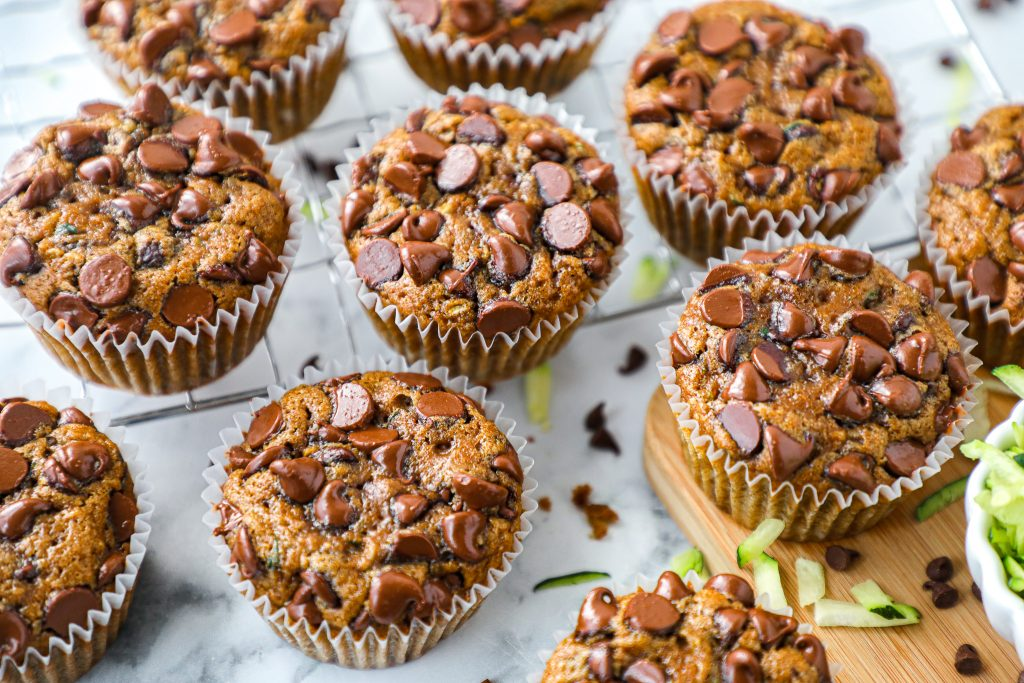A batch of healthy chocolate chip zucchini muffins made with grated zucchini and gooey chocolate chips. It's a quick and easy recipe that everyone will love!