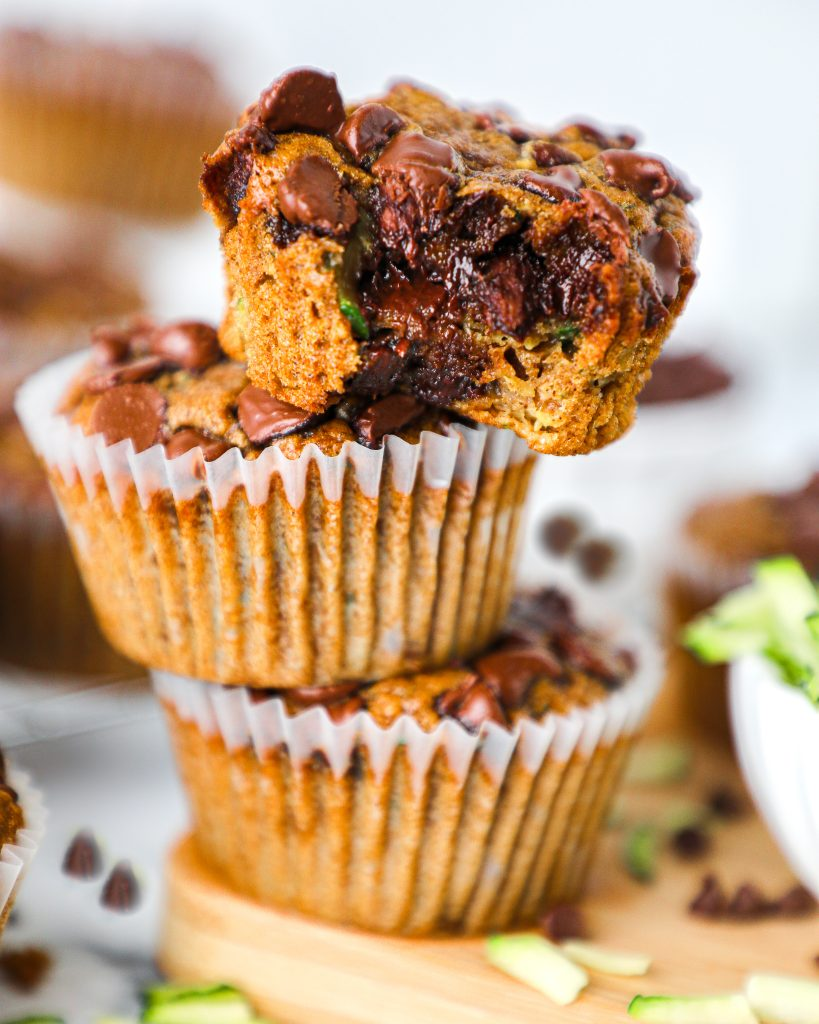 3 warm chocolate chip zucchini muffins stacked on top of each other with a bite taken out of one. These pastries are loaded with chocolate, vegetables and other nutrients too!