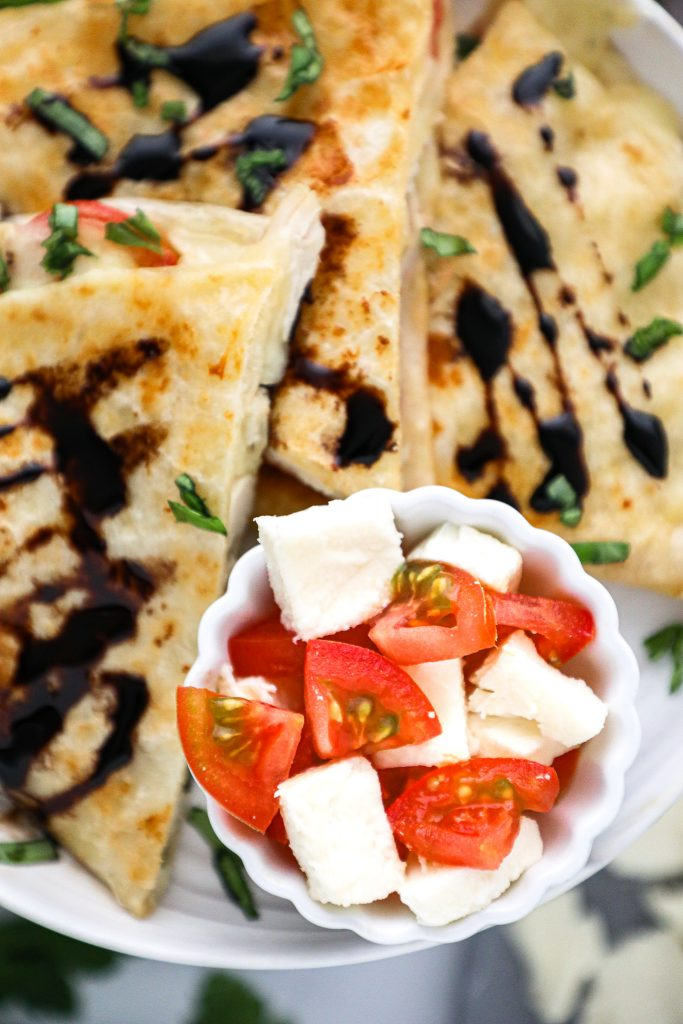 A close up picture of tomato slices and mozzarella which are some of the main ingredients in these chicken caprese quesadillas!