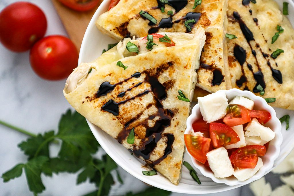 An incredibly easy lunch or dinner idea that involves everything you love about caprese all stuffed into a crispy tortilla! Plus there's a recipe for some homemade balsamic glaze too!