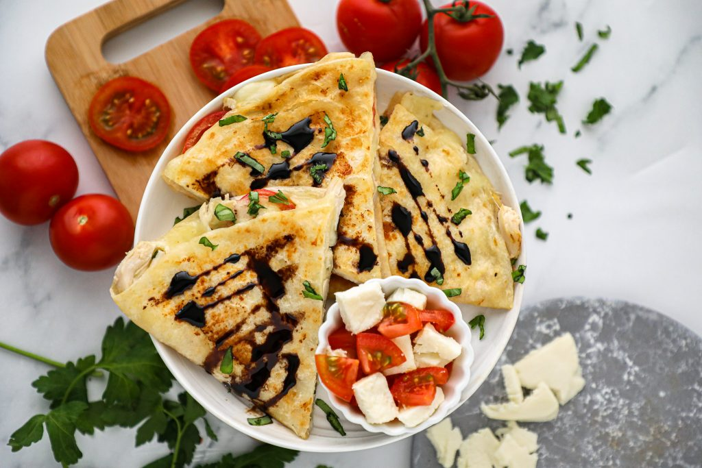 These tasty chicken caprese quesadillas are so flavorful and easy to make! They're loaded with cheese, tomatoes and chicken and serve with a flavorful balsamic reduction!