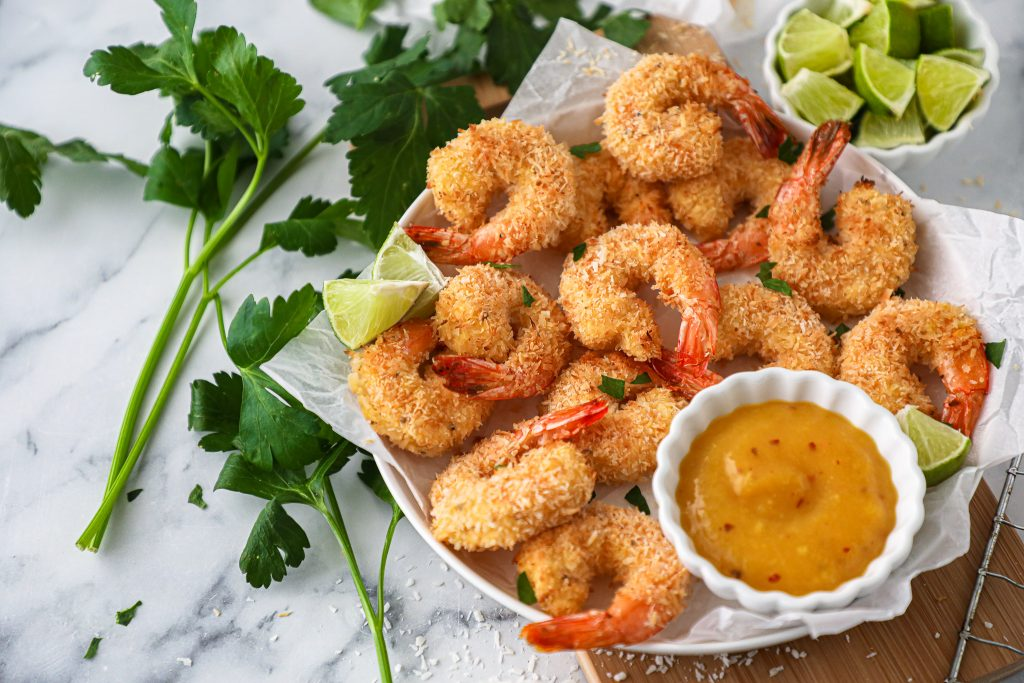 Crispy, crunchy and baked to perfection! This healthy shrimp dish is made with shredded coconut, island spices and coconut flour and is served with an tangy mango lime sauce!