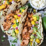 Spicy salmon, fresh mango salsa and lots of crunchy green cabbage! These easy fish tacos are perfect for summer and just what you need this Cinco de Mayo!