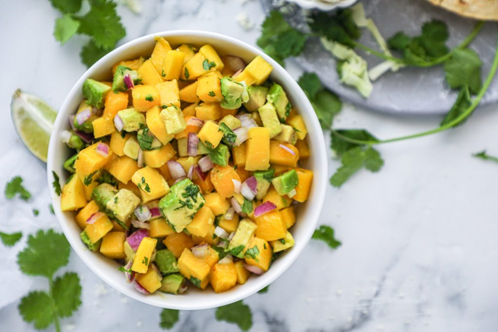Fresh and easy mango salsa made with mangoes, avocado, red onion, cilantro and lime juice! It's the perfect summer condiment!