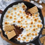 S'mores skillet dip is a great way to upgrade your favorite summer treat! It has a layer of rich melted chocolate topped with gooey marshmallows and all served with graham crackers for dipping!