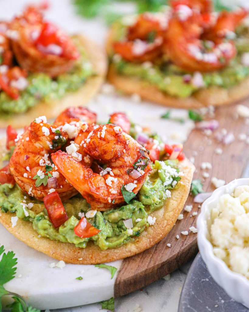 Add some Mexican flare to weeknight dinner routine with these healthy spicy shrimp tostadas! They're made with chili lime shrimp, homemade guacamole and crispy baked tostada shells!