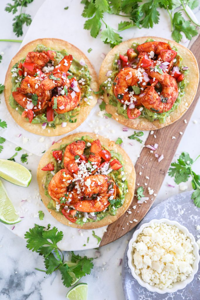 Spicy shrimp and creamy guacamole are served on top of a crispy tostada shell with all the taco fixings! This is one easy meal you won't get enough of!