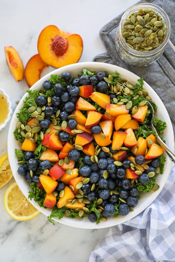 An easy peach and kale salad that's made with only 4 ingredients and tastes amazing too! This will even turn kale haters into kale lovers!