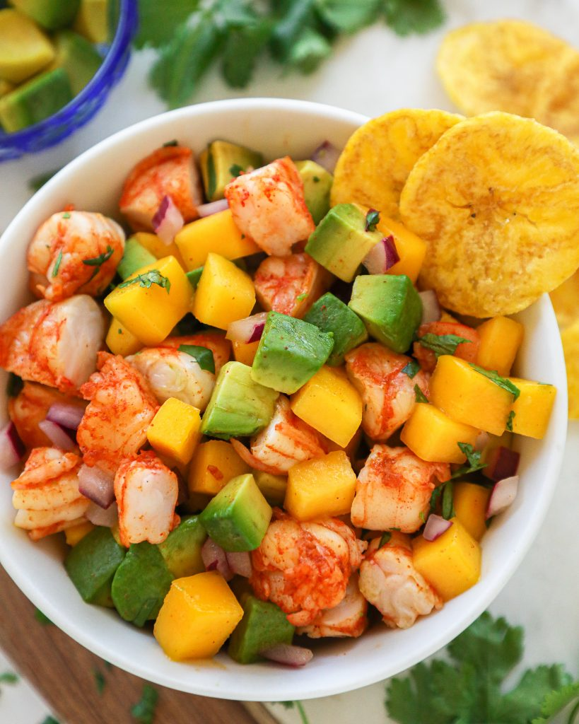 Spicy shrimp, mango and avocado salad in a white bowl served with plantain chips on the side