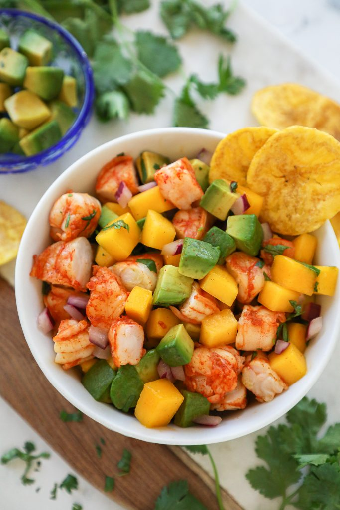 Close up of cold shrimp, mango and avocado salad in a small white bowl surrounded by cilantro