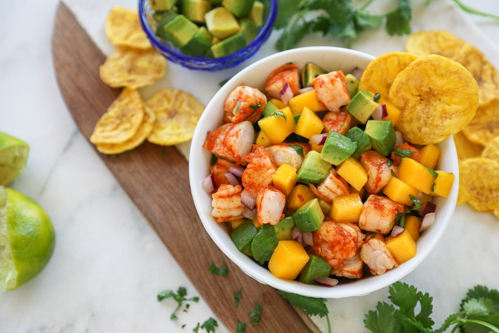 A bowl of tropical shrimp salad sitting on a marble countertop surrounded by plantain chips, lime wedges and cilantro