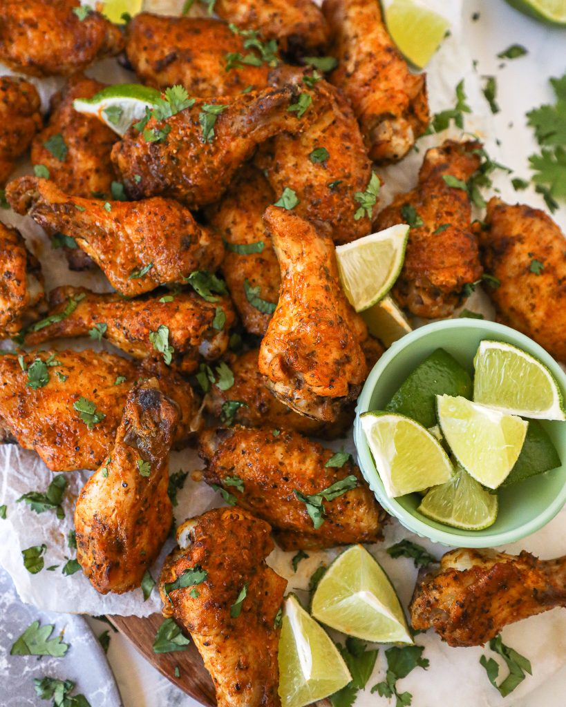 Cilantro lime chicken wings on a white platter served with extra lime wedges on the side