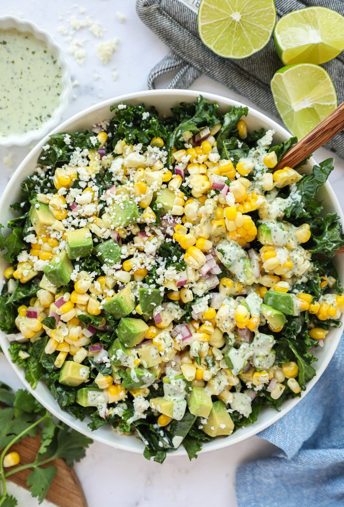 A delicious salad recipe made with kale, sweet corn, red onion, cotija cheese, avocado and an easy cilantro lime dressing! It's so perfect for summer!